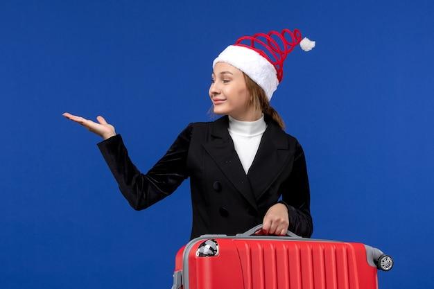 Giovane femmina di vista frontale che trasporta borsa rossa sulla donna di vacanza di vacanze di viaggio dello scrittorio blu