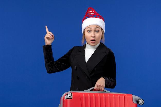 Vista frontale giovane femmina che trasporta borsa rossa su una vacanza donna viaggio vacanza scrivania blu