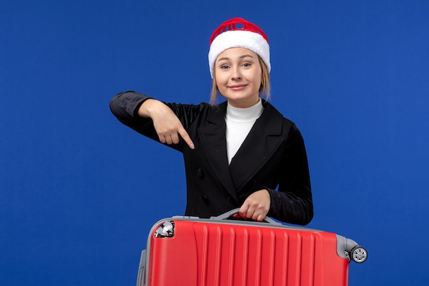 Giovane femmina di vista frontale che trasporta borsa rossa sulla donna di vacanza di vacanza di viaggio della parete blu