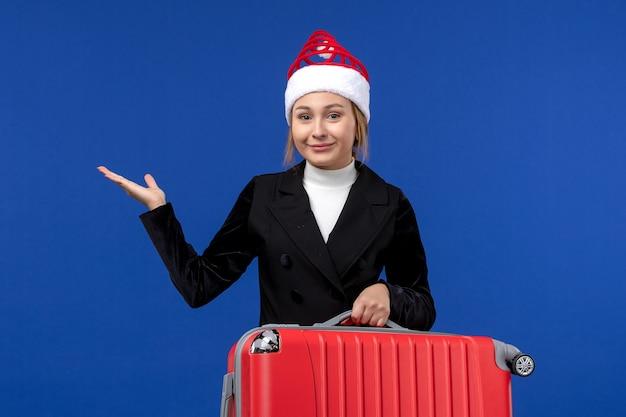 Вид спереди молодая женщина, несущая красную сумку на синей стене, поездка, отпуск, отпуск, женщина
