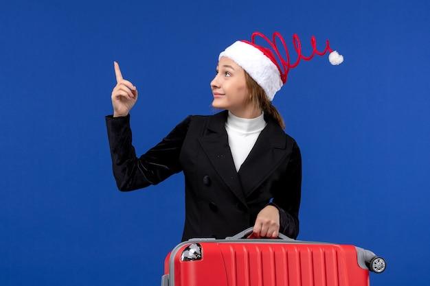 青い壁の休暇旅行の女性の休日に赤いバッグを運ぶ正面図若い女性