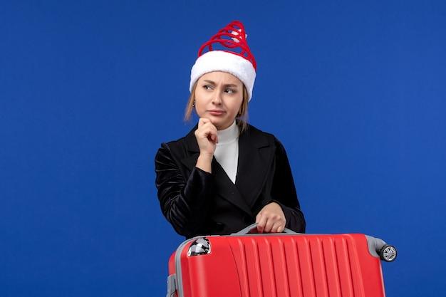 Вид спереди молодая женщина, несущая красную сумку на синем столе, праздник, отпуск, поездка, женщина