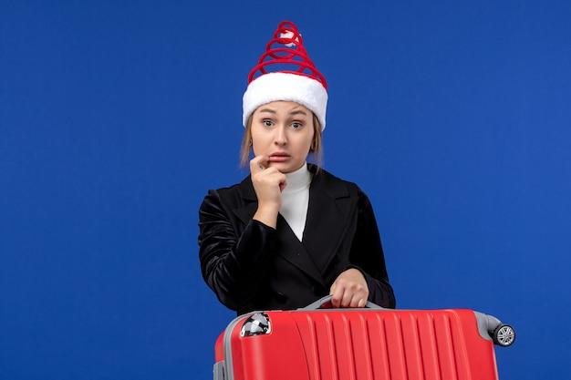 Вид спереди молодая женщина, несущая красную сумку на синем полу, праздник, отпуск, поездка, женщина