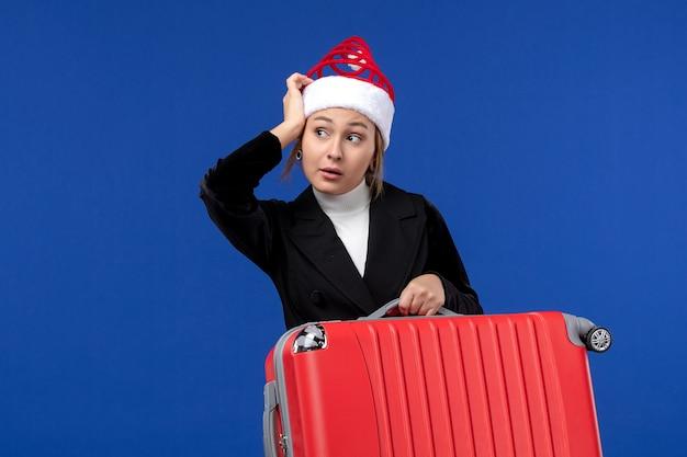 青い壁の休日の休暇旅行の女性に赤いバッグを運ぶ正面図若い女性