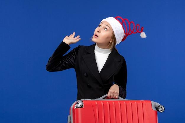 正面図青い壁に赤いバッグを運ぶ若い女性休暇飛行女性休日