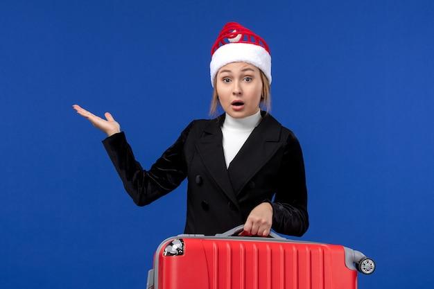 Вид спереди молодая женщина, несущая красную сумку на синей стене, отпуск, поездка, женщина, праздник