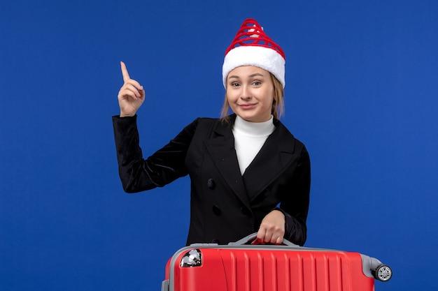 Вид спереди молодая женщина, несущая красную сумку на синей стене, отпуск, поездка, женщина, праздники