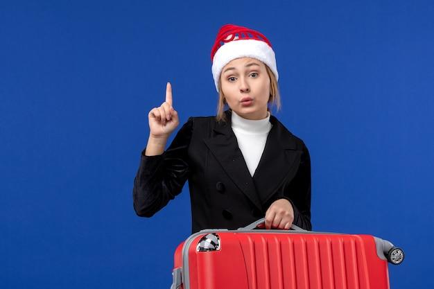 水色の壁の休日の休暇旅行の女性に赤いバッグを運ぶ正面図若い女性