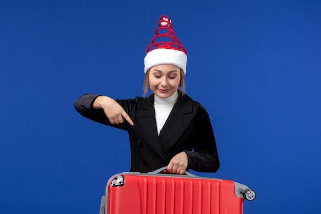 Вид спереди молодая женщина, несущая красную сумку на голубой стене, праздник, отпуск, поездка, женщина