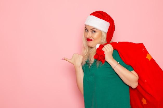 Vista frontale giovane femmina che trasporta borsa rossa con regali sulla parete rosa modello vacanza capodanno foto a colori santa