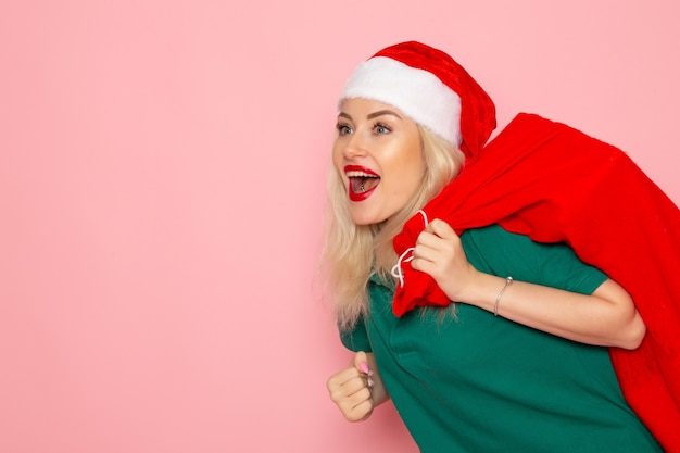 Front view young female carrying red bag with presents on the pink wall model holiday xmas new year photo color santa