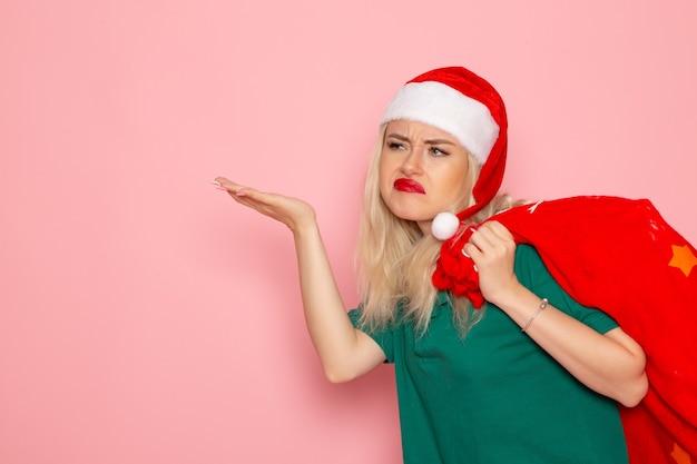 Vista frontale giovane femmina che trasporta borsa rossa con regali sulla parete rosa modello natale capodanno colore santa vacanza