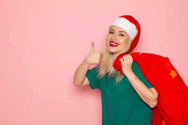 Vista frontale giovane femmina che trasporta borsa rossa con regali sulla parete rosa modello natale capodanno foto colore santa vacanza