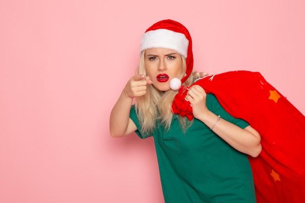 Vista frontale giovane femmina che trasporta borsa rossa con regali sulla parete rosa modello natale capodanno foto santa vacanza