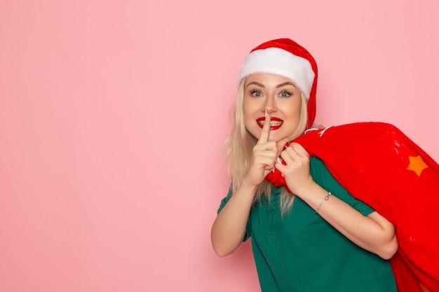 Vista frontale giovane femmina che trasportano borsa rossa con regali sulla parete rosa natale capodanno foto colore santa vacanza