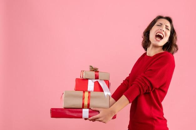 Вид спереди молодая женщина, несущая рождественские подарки на розовом столе, рождественский праздник, эмоция, женщина, новый год