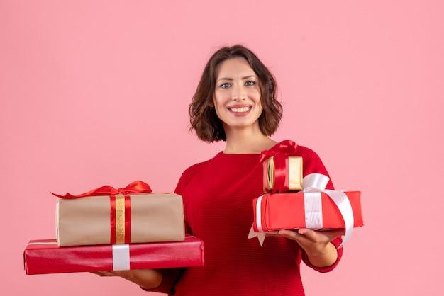 핑크에 크리스마스 선물을 들고 전면보기 젊은 여성