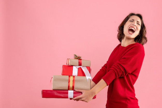 Front view young female carrying xmas presents on pink desk christmas holiday emotion woman new year