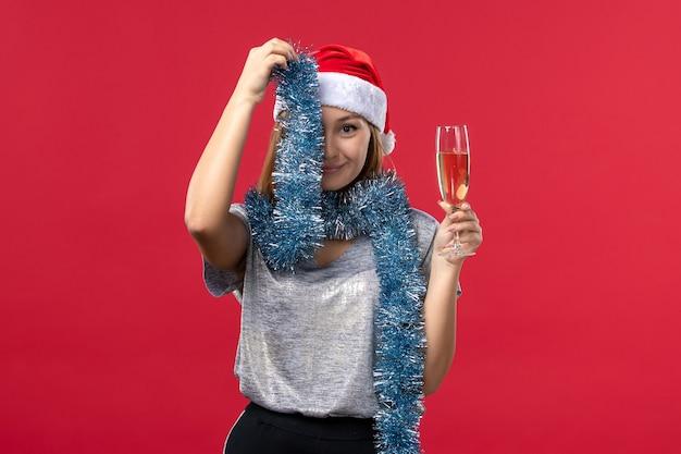 赤い壁のクリスマス休暇の色で新年を祝う正面図若い女性