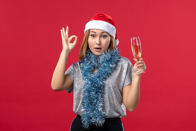赤い壁のクリスマスパーティーの休日に新年を祝う正面図若い女性