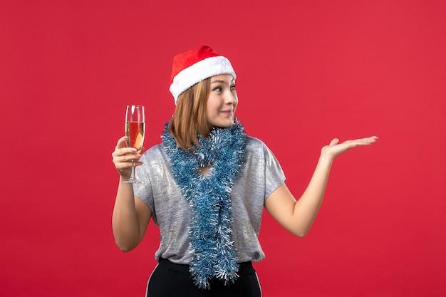 赤い壁の色のクリスマス休暇で新年を祝う正面図若い女性
