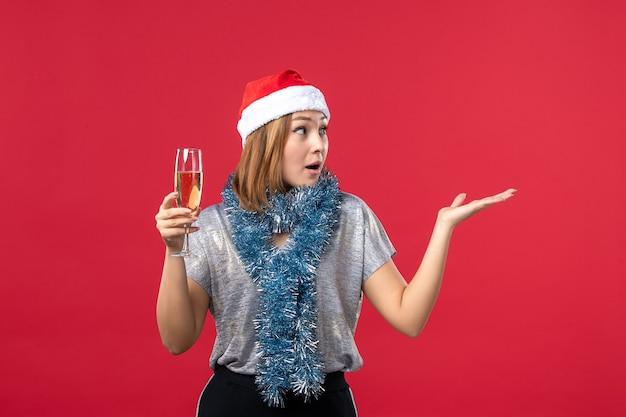 빨간 벽 휴일 색상 크리스마스에 새 해를 축 하하는 전면보기 젊은 여성