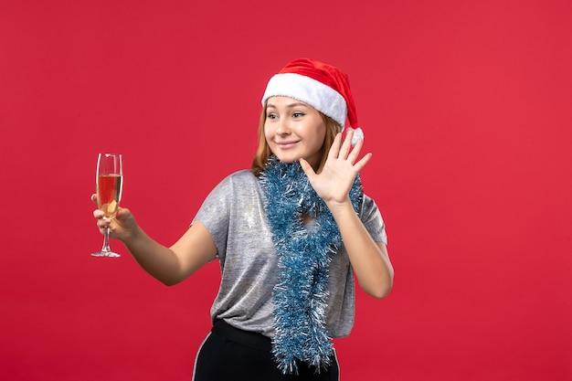 赤い床のクリスマス休暇の色で新年を祝う正面図若い女性