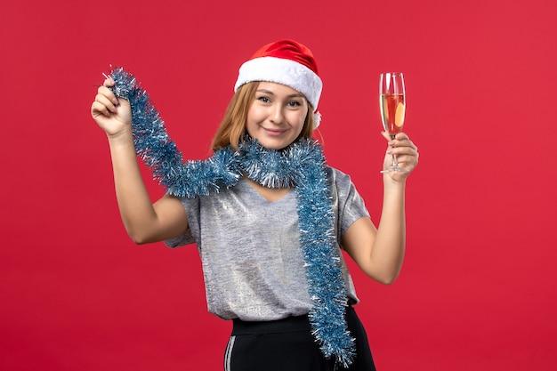 赤い床のクリスマスパーティーの休日に新年を祝う正面図若い女性