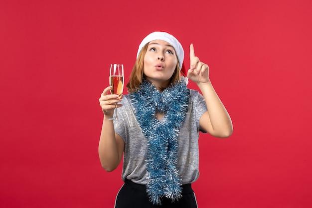 Вид спереди молодая женщина празднует новый год на красном полу праздничного цвета рождество