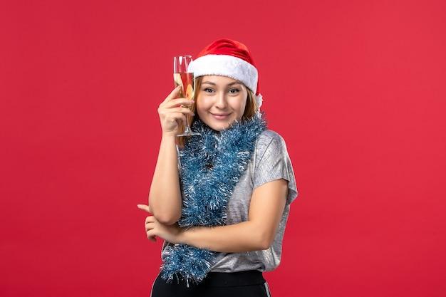 赤い壁の休日の色のクリスマスに新年を祝う正面図若い女性