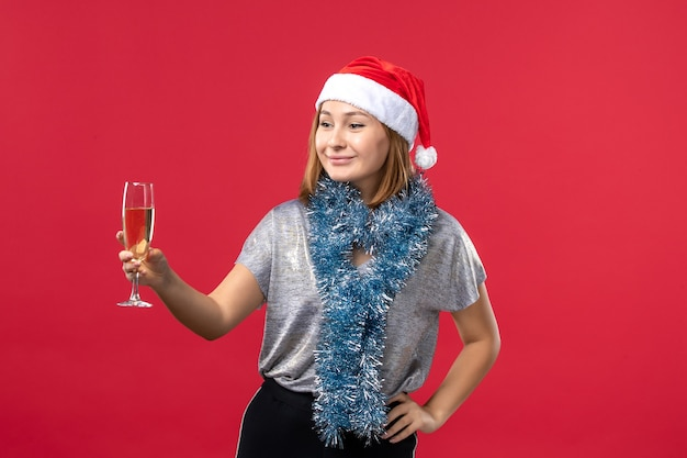 Front view young female celebrating new year on the red wall christmas holiday color