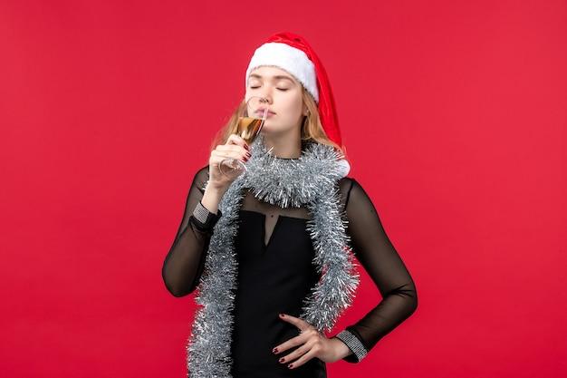 Вид спереди молодая женщина празднует новый год с шампанским на красной стене рождественского цвета