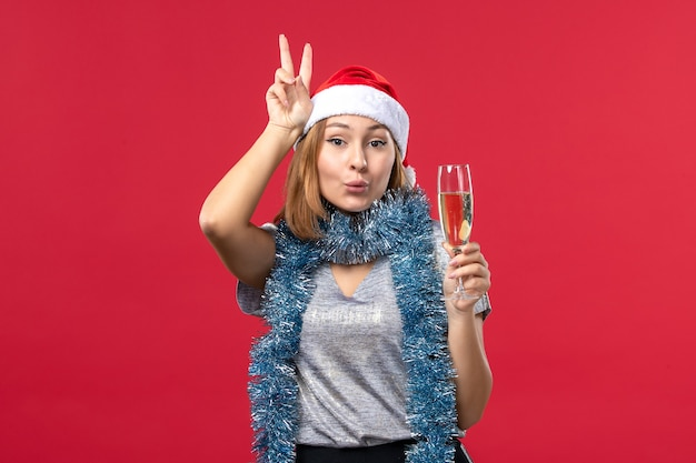 Front view young female celebrating new years coming on red desk color christmas holiday