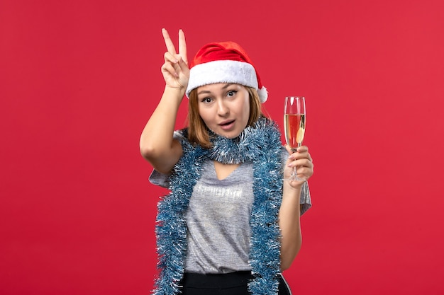 Front view young female celebrating new years coming on a red wall color christmas holiday