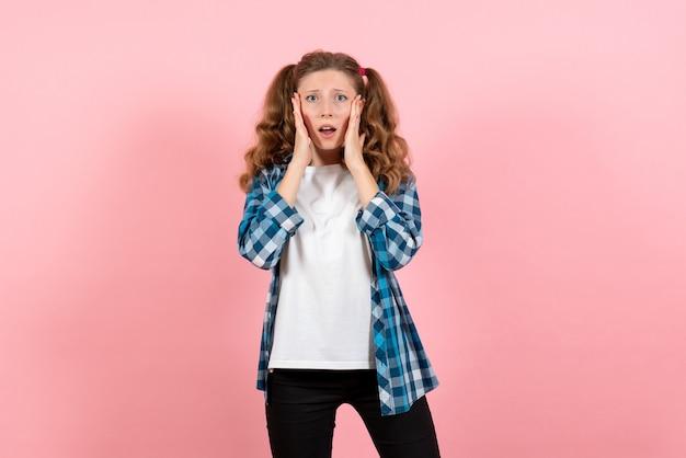 Vista frontale giovane femmina in camicia a scacchi in posa sullo sfondo rosa modello emozioni ragazzino gioventù donna ragazza