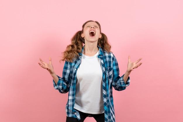 Vista frontale giovane femmina in camicia a scacchi in posa su sfondo rosa modello gioventù donna emozioni bambino colore