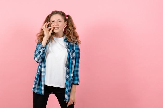 Vista frontale giovane femmina in camicia a scacchi in posa su sfondo rosa modello di emozione di colore della gioventù del bambino della donna
