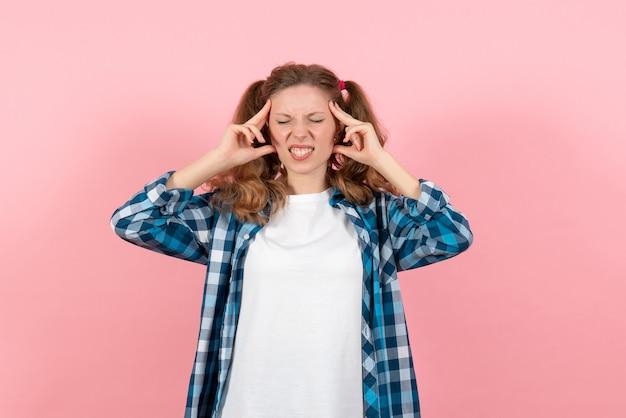 Giovane donna di vista frontale in camicia a scacchi in posa su sfondo rosa modello giovanile emozioni donna bambino ragazza