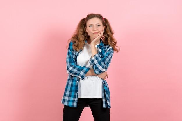 Vista frontale giovane femmina in camicia a scacchi in posa su sfondo rosa gioventù donna colore emozione modello kid