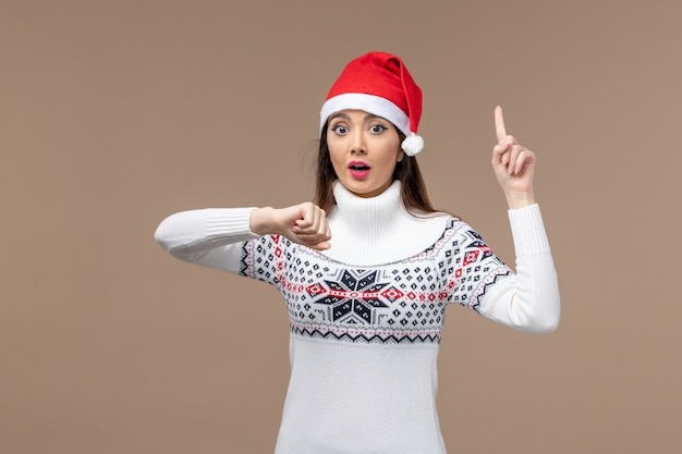 갈색 배경 감정 크리스마스 새 해에 시간을 확인하는 전면보기 젊은 여성