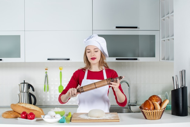 Front view young female chef holding up rolling pin in the kitchen