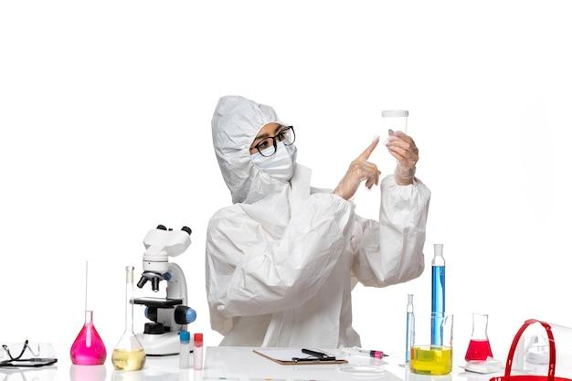 밝은 흰색 배경 실험실 covid- 화학 바이러스 건강에 빈 플라스크를 들고 특수 보호 복에 전면보기 젊은 여성 화학자