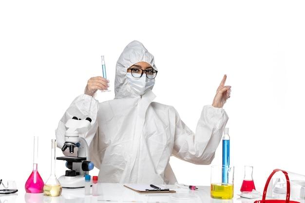 흰색 배경 실험실 covid 화학 바이러스에 파란색 솔루션 플라스크를 들고 특수 보호 복에 전면보기 젊은 여성 화학자