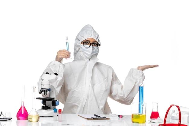 흰색 책상 실험실 covid 화학 바이러스에 파란색 솔루션으로 플라스크를 들고 특수 보호 복에 전면보기 젊은 여성 화학자
