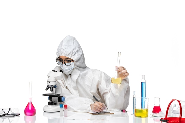 솔루션 플라스크를 들고 흰색 배경 실험실 covid 화학 바이러스에 현미경을 사용하는 특수 보호 복에 전면보기 젊은 여성 화학자