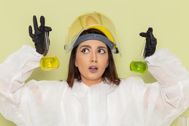 Вид спереди молодая женщина-химик в специальном защитном костюме, держащая колбы с растворами на зеленом столе, химическая химия, женская научная лаборатория