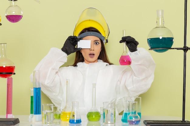 Вид спереди молодая женщина-химик в специальном защитном костюме, держащая раствор и карточку на зеленой стене, химическая химия, женская научная лаборатория