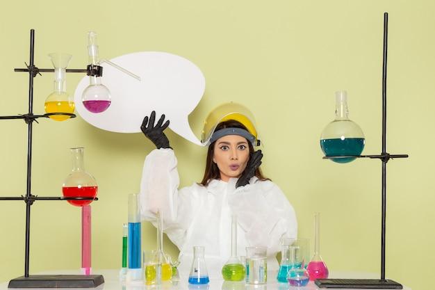 녹색 벽 작업 화학 실험실 화학 여성 과학에 흰색 기호를 들고 특수 보호 복에 전면보기 젊은 여성 화학자