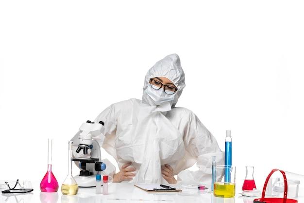 흰색 배경 바이러스 실험실 covid- 화학에 솔루션으로 가득한 테이블에 앉아 특수 보호 복에 전면보기 젊은 여성 화학자