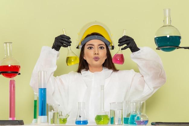 グリーンデスクの化学実験室の化学の仕事の女性の科学のソリューションで作業している特別な防護服の正面図若い女性の化学者